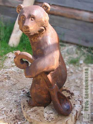 Carved wooden bear with a ladle