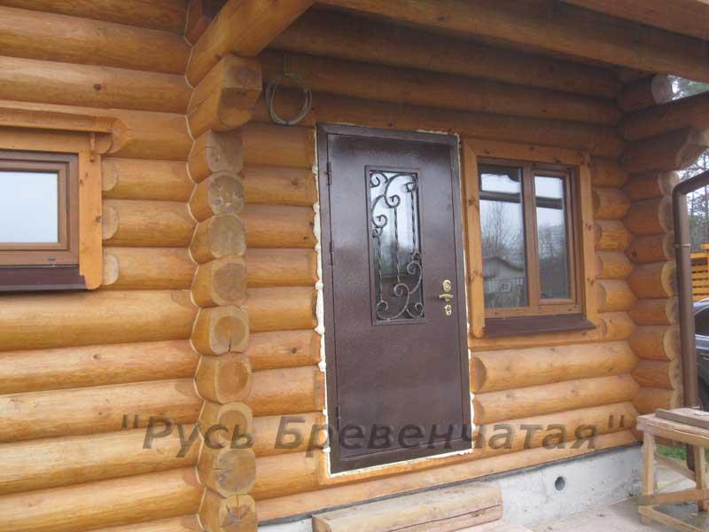 металлическая дверь в доме из бревна